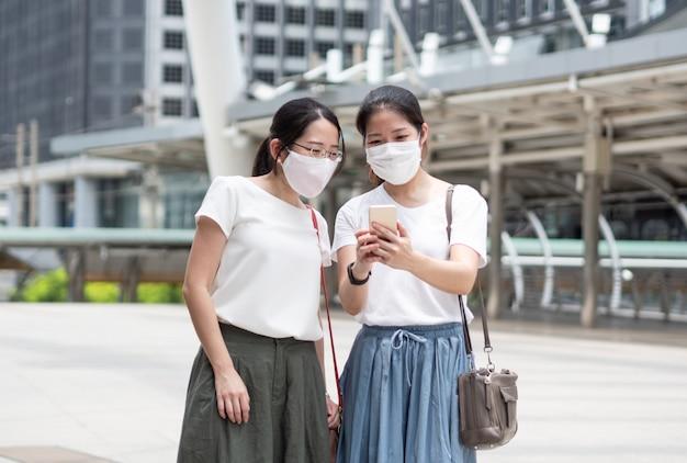 Twee aziatische vrouwen die elke keer buitenshuis een medisch gezichtsmasker dragen, als nieuwe normale trend en zelfbescherming, smartphone gebruiken voor selfie of bedrijfsinformatie zoeken