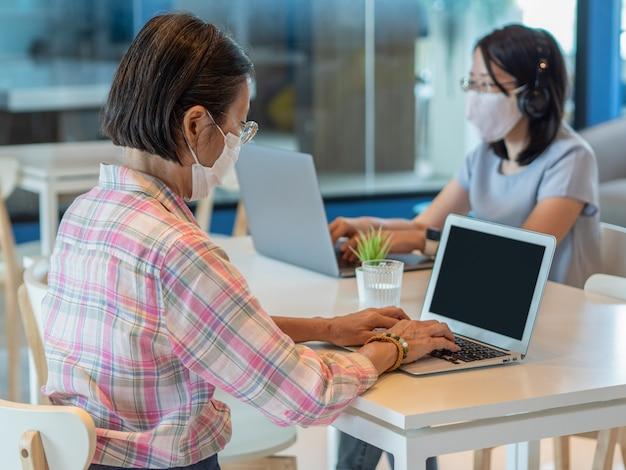 Twee aziatische vrouwen die gezichtsmasker dragen en smartphone en laptop voor videogesprek of het werken gebruiken, zitten op afzonderlijke lijsten om veiligheids sociale afstand te houden, als nieuw normaal levensstijlconcept.