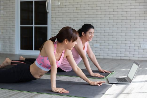 Twee aziatische vrouwen die laptop kijken om yogatraining van internet te leren