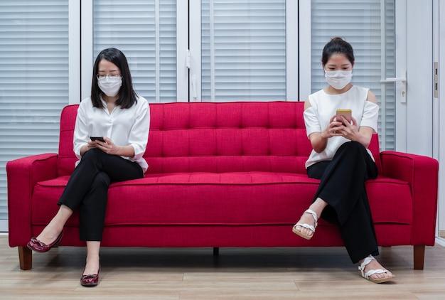 Twee aziatische vrouwen die maskers dragen die thuis werken of op afstand werken met een smartphone om de verspreiding van coronavirusinfectie tijdens de covid-19-uitbraak te verminderen.