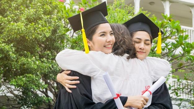 Twee aziatische vrouwen glimlachen gelukkig in graduatietoga's en glb en bevinden zich met de ouder