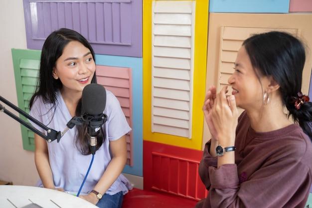 Twee aziatische vrouwen maken een grapje met handengebaar met microfoon tijdens podcast