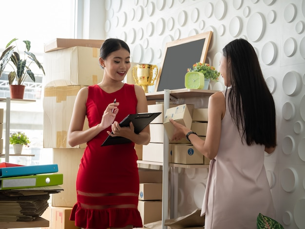 Twee aziatische vrouwen met het start kleine bedrijfs freelance ondernemer thuis werken. het controleren van de productbestelling.