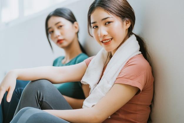 Twee aziatische vrouwen nemen een pauze van yogasessie