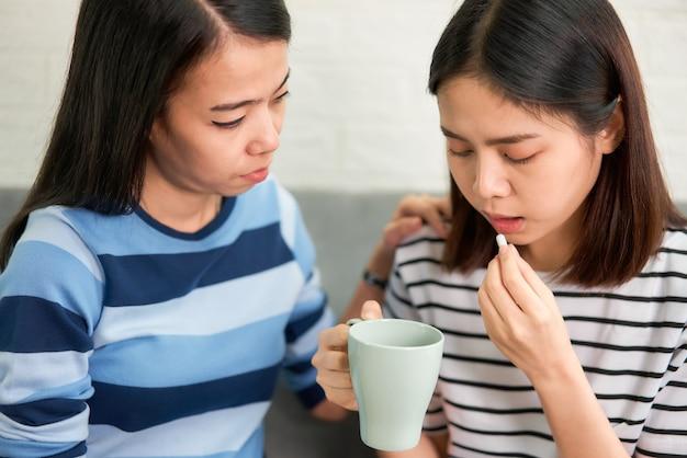 Twee aziatische vrouwen nemen witte pil in de mond en drinkwater in glas op de bank in huis, voelt zich ziek. gezondheidszorg concept.