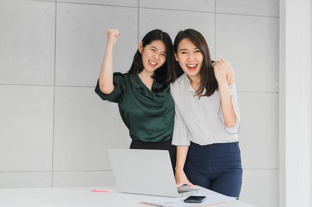 Twee aziatische vrouwenvrienden vieren succes