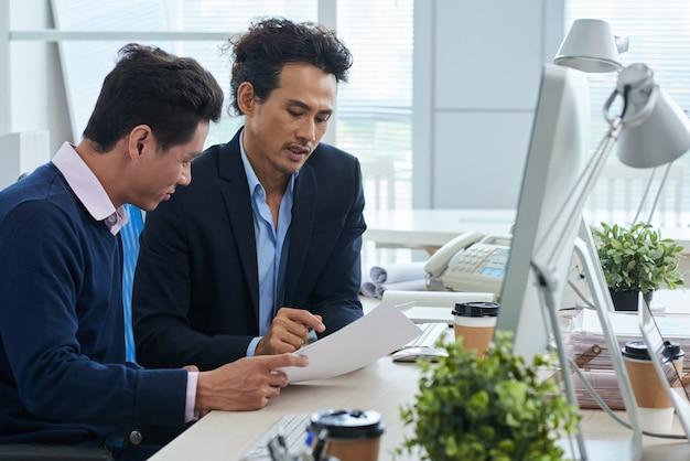 Twee aziatische zakenlieden die bij bureau samen zitten en document bespreken