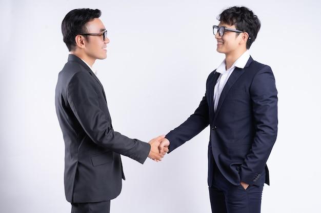 Twee aziatische zakenlieden die handen schudden op een witte achtergrond
