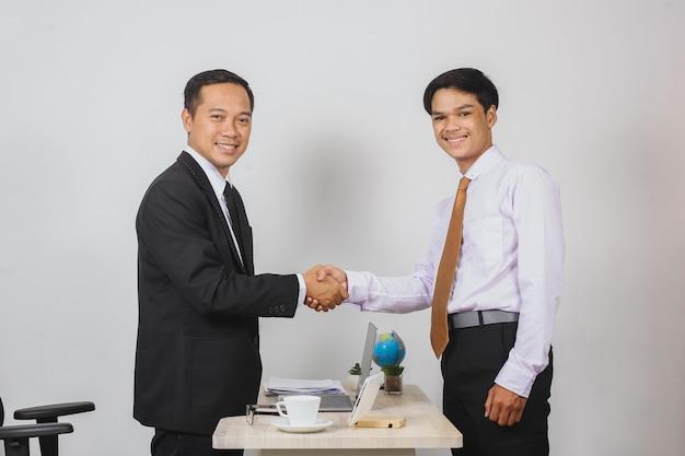 Twee aziatische zakenlieden die handen schudden terwijl ze naar de camera kijken tussen het bureau voor een dealconcept
