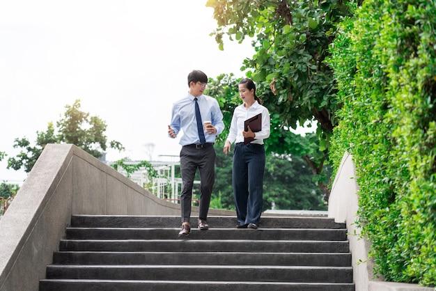 Twee aziatische zakenmedewerkers buiten kantoorgebouwen bespreken en becommentariëren werk met elkaar.