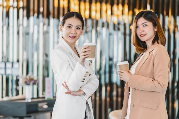 Twee aziatische zakenvrouwen praten tijdens koffiepauze in moderne kantoor of coworking ruimte, koffiepauze, ontspannen en praten na werktijd, zakelijke en mensen partnerschap concept