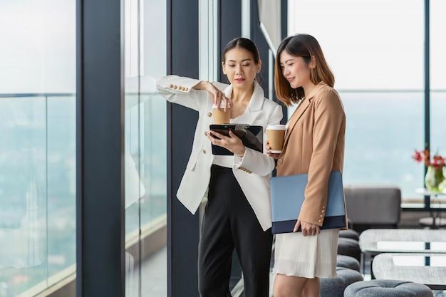 Twee aziatische zakenvrouwen praten tijdens koffiepauze in moderne kantoor of naaiatelier ruimte