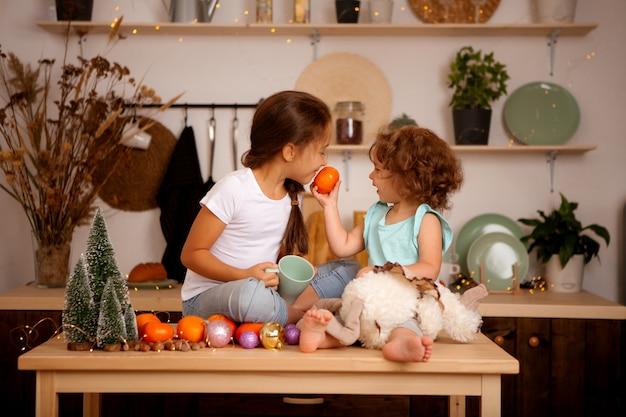 Twee baby meisjes mandarijnen eten in de keuken van kerstmis