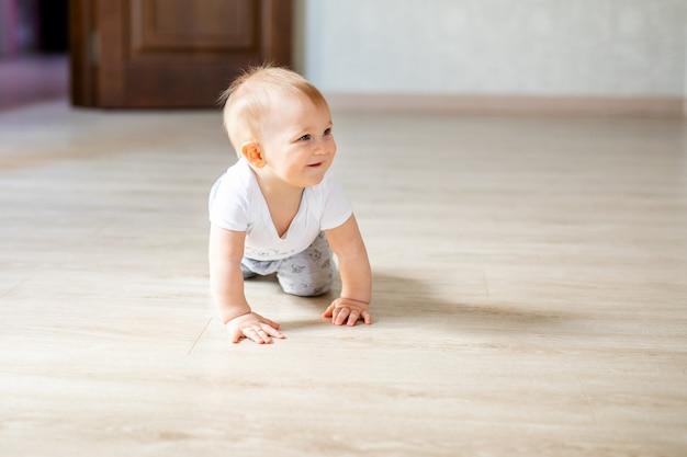 Twee baby's jongen en meisje schaken thuis op de witte houten vloer.