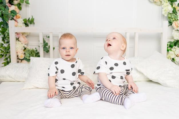 Twee baby-tweeling 8 maanden oud zittend op het bed in dezelfde kleding, broer-zus relatie, modieuze kleding voor kinderen van een tweeling