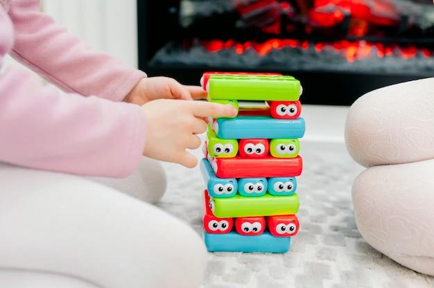 Twee babymeisjes spelen het kinderspel jeng. trek een stuk uit de jenga-toren. verwijder voorzichtig een stuk jenga uit de toren. bordspellen