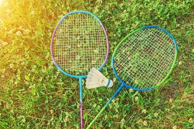 Twee badmintonracket met shuttle op groen gras. badminton openluchtspelactiviteit. badminton buitensport spelen.