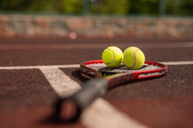 Twee ballen voor het spelen van tennis op racket die de witte lijn van sportspeeltuin overschrijden