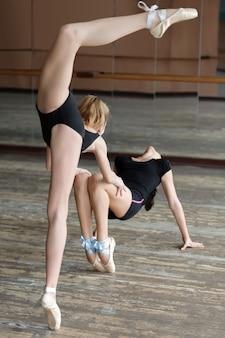 Twee ballerina's die in de studio repeteren