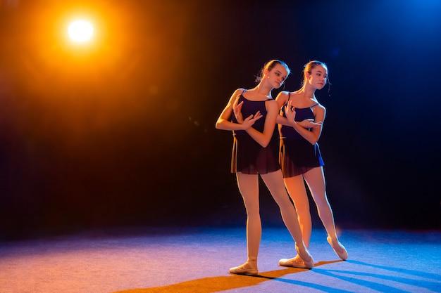 Twee ballerina's in zwarte jurk poseren verlicht door veelkleurige stralen van schijnwerpers
