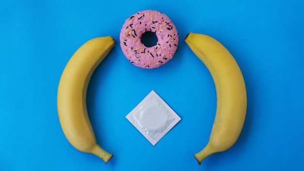 Twee bananen en een roze donut op een blauwe achtergrond. condoom en beschermde seks