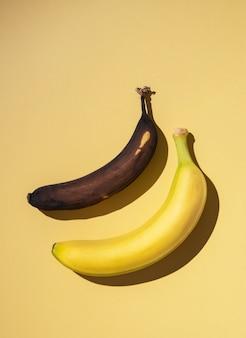 Twee bananen, vers en lelijk, op een gele achtergrond met een harde schaduw