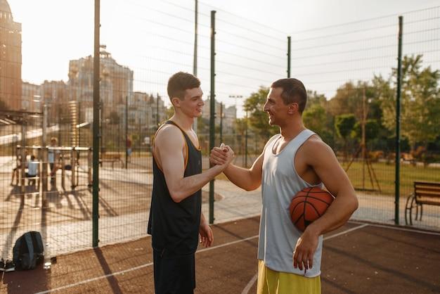 Twee basketballers schudden elkaar de hand na het spelen op de buitenbaan