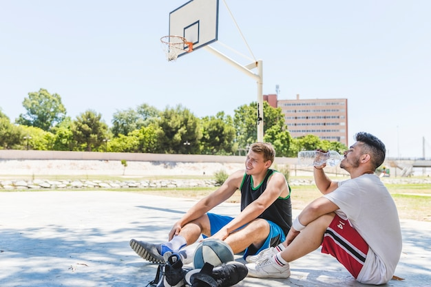 Twee basketbalspeler die bij in openlucht hof ontspannen