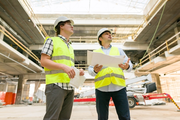 Twee bedrijfsbouwersmensen bij bouwwerf. bouwer, inspecteur, ingenieur, architect, klant, mensen die in het gebouw werken