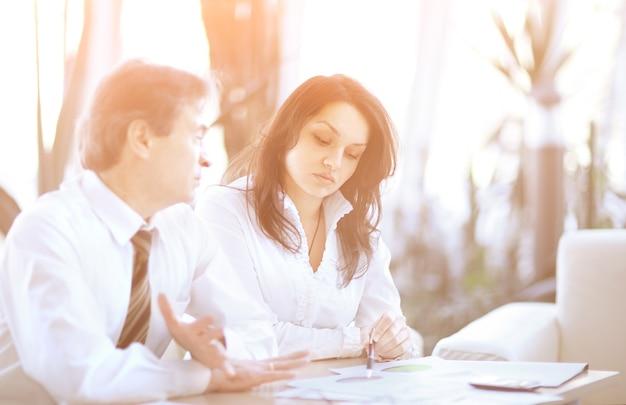 Twee bedrijfscollega's die een financieel rapport bespreken