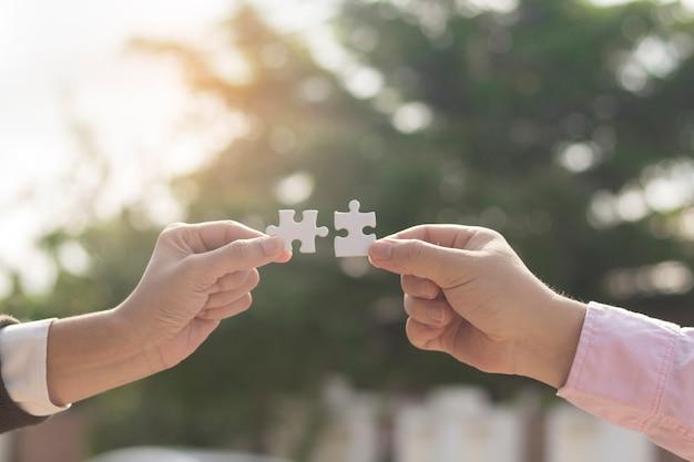 Twee bedrijfshanden die het stuk van het paarraadsel met zonsondergangachtergrond proberen te verbinden