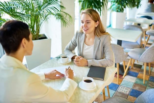 Twee bedrijfsvrouwen die bij koffiepauze samenkomen