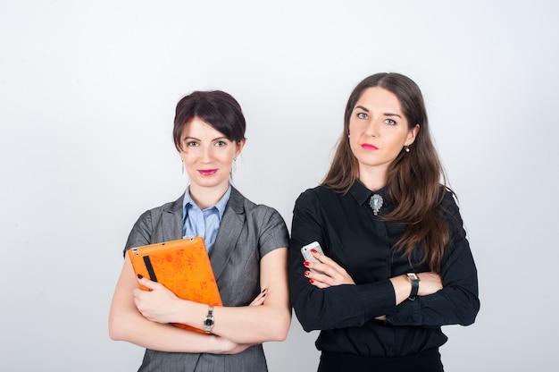 Twee bedrijfsvrouwen die zich op een licht met uw gekruiste wapens bevinden