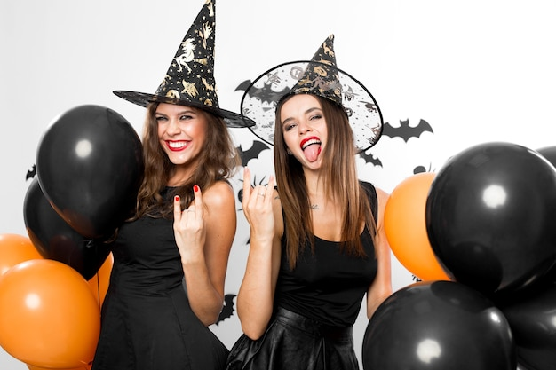 Twee beeldschone vrouwen in zwarte jurken en heksenhoeden trekken een grimas en houden zwarte en oranje ballonnen vast. halloween.