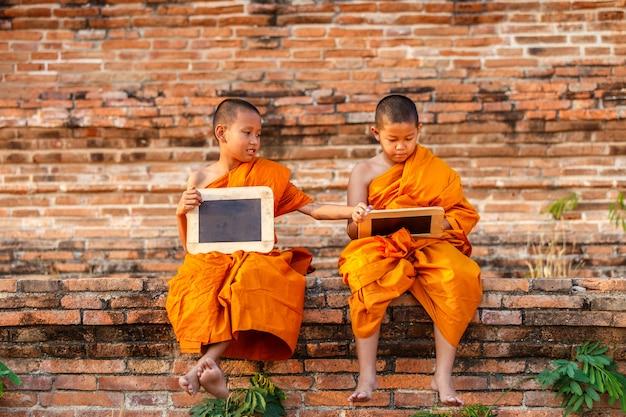 Twee beginner lezing en het bestuderen van bord met grappig in oude tempel in zonsondergangtijd