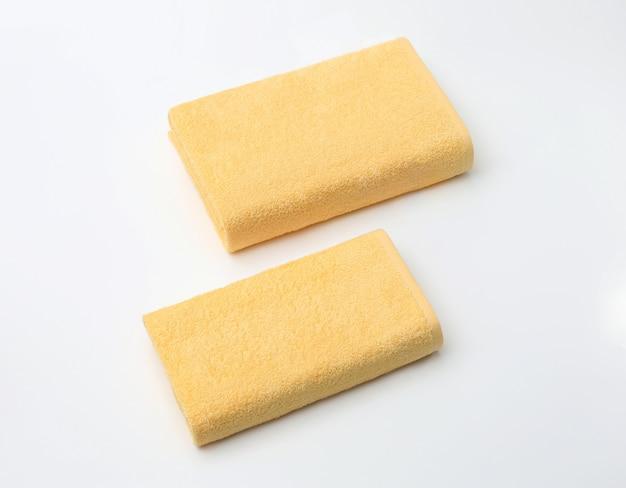 Twee beige badstofhanddoeken vouwden op wit
