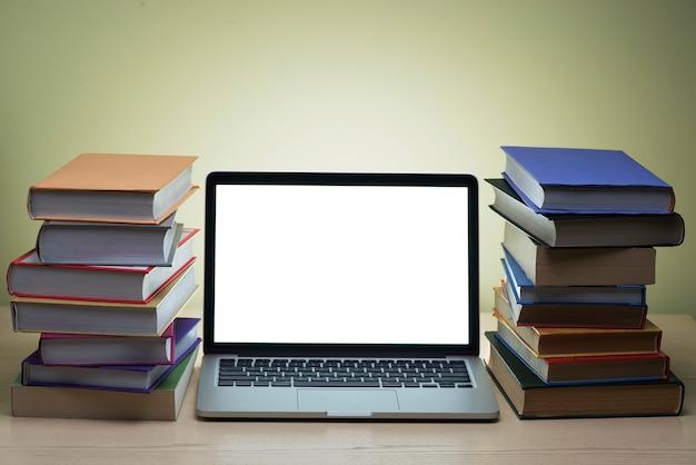 Twee bergen van boeken naast een laptop met een helder scherm