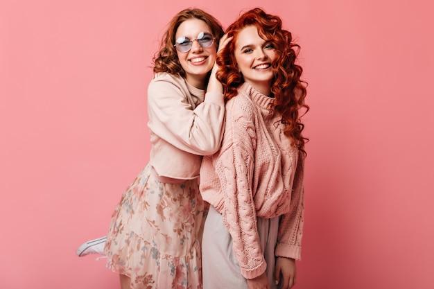 Twee beste vrienden die camera met glimlach bekijken. studio shot van vrolijke glamoureuze meisjes geïsoleerd op roze achtergrond.