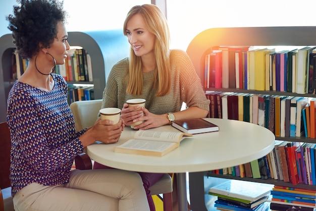 Twee beste vrienden die koffie drinken over goede boeken