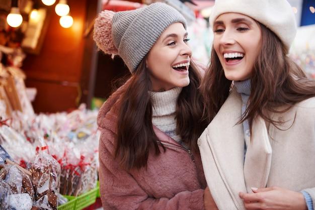 Twee beste vrienden die plezier hebben op de kerstmarkt