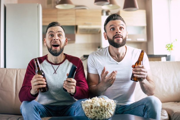 Twee beste vrienden en fans van voetbal kijken naar een sportwedstrijd op de tv en drinken bier en eten snacks terwijl ze juichen voor het team op de bank