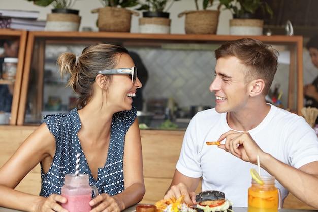 Twee beste vrienden genieten van een leuke tijd samen tijdens de lunch, eten en lachen om grappen, kijken elkaar aan en herinneren zich de goede oude tijd van hun vriendschap