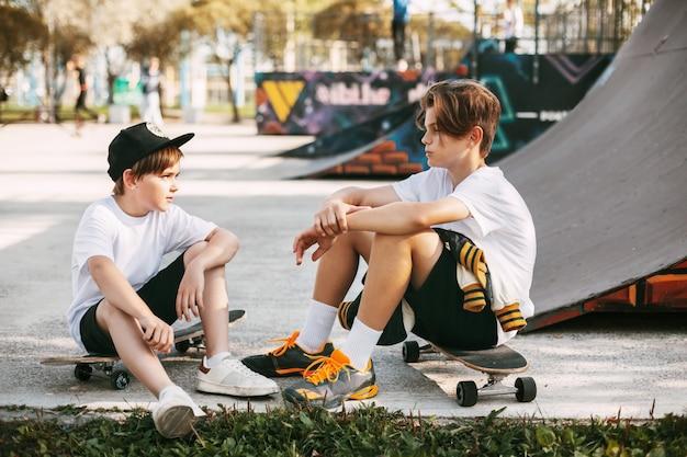 Twee beste vrienden in een skateboardpark. vrienden zitten op schaatsen in het park, praten en glimlachen