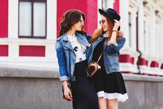Twee beste vrienden lopend en pratend buiten op straat in het stadscentrum