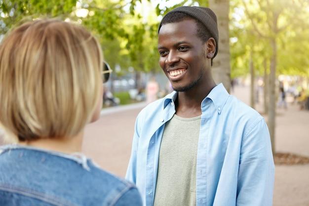 Twee beste vrienden ontmoeten elkaar op straat: een man met een donkere huidskleur in trendy hoed en overhemd, breed glimlachend terwijl ze een gesprek heeft met zijn vriendin, blij haar per ongeluk te ontmoeten in het groene park