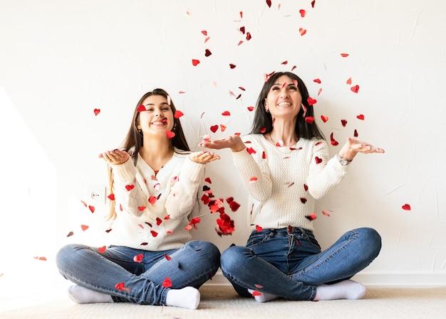 Twee beste vrienden plezier thuis blazen rood hart vorm confetti