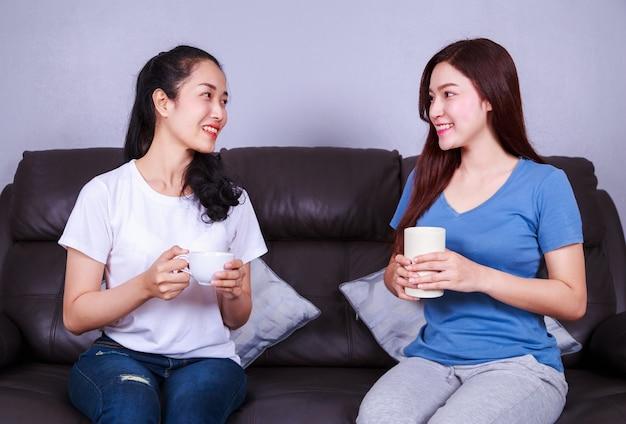 Twee beste vrienden praten en een kopje koffie drinken op de sofa in de woonkamer