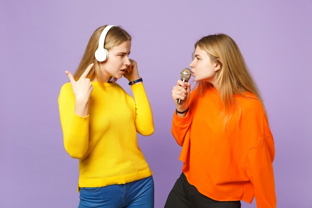 Twee betrokken blonde tweelingzusters meisjes in levendige kleding luisteren muziek met koptelefoon zingen lied in microfoon geïsoleerd op violet blauwe muur. mensen familie levensstijl concept.