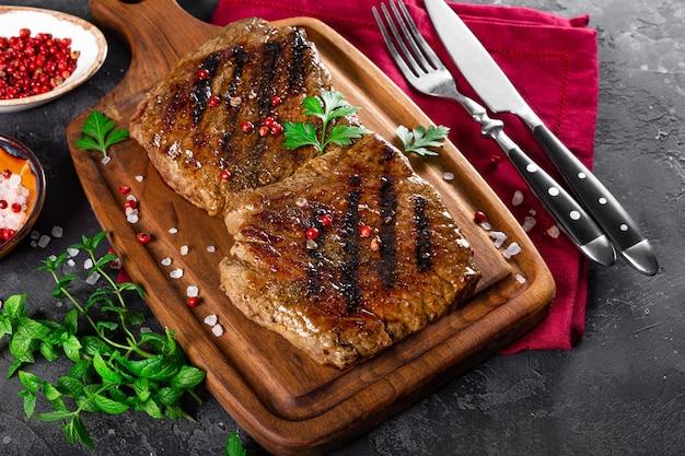 Twee biefstukken gekookt op de grill op een houten snijplank close-up.