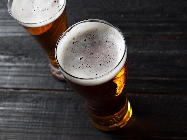 Twee bieren op een donkere houten tafel